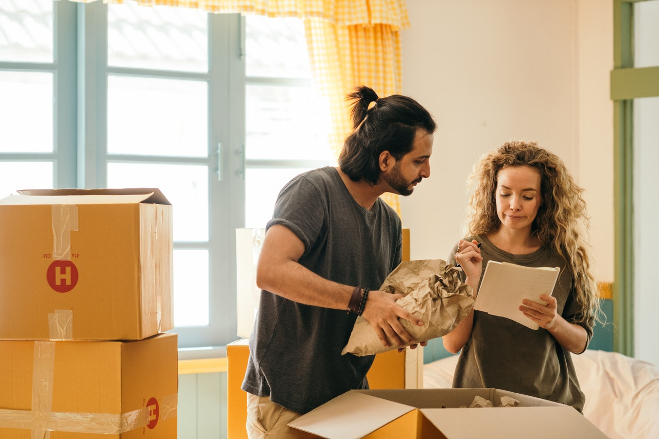A couple packing for a move following Room-by-room packing guidelines.