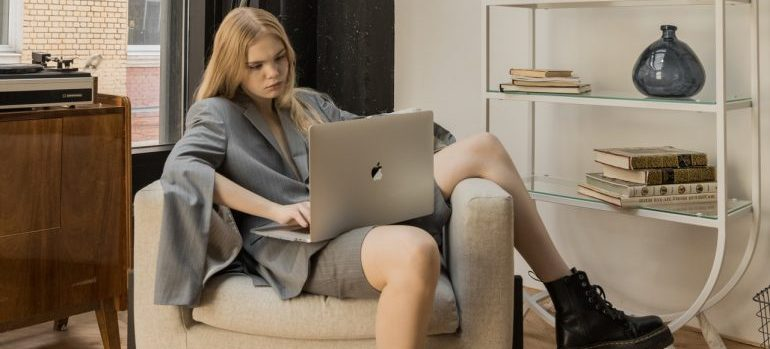 A young woman making a moving plan on her laptop.
