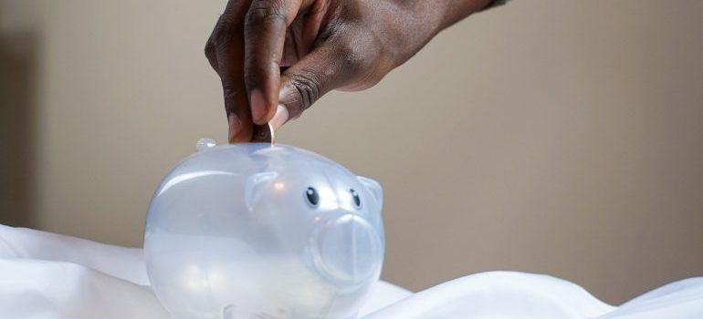 person putting money in a piggy bank
