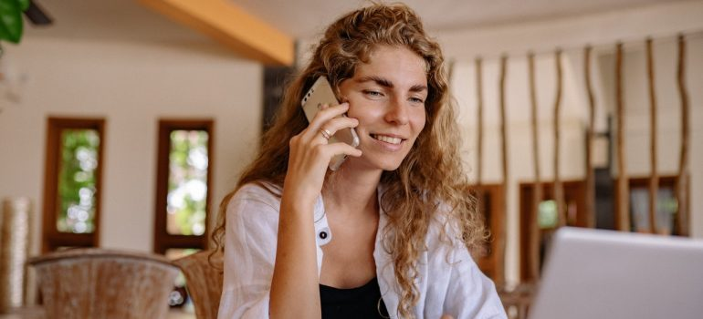 A smiling woman talking on the phone with Chinatown movers