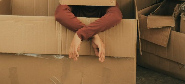 person surrounded by boxes