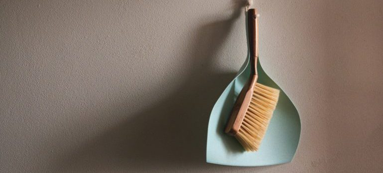 A dustpan and brush on the wall.