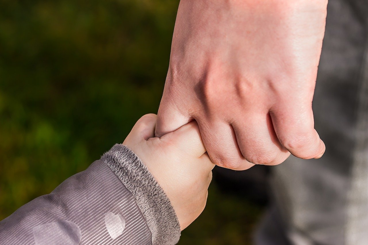 A person holding a child's hand.