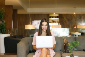 A woman sitting on a sofa with a laptop - home office in Financial District