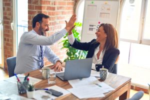 man and woman in an office high fiving because they know all the ways valet storage simplifies commercial relocation