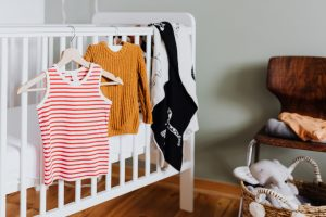 baby clothes hanging from hangers on a crib