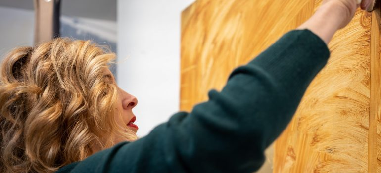 A woman taking artwork off a wall
