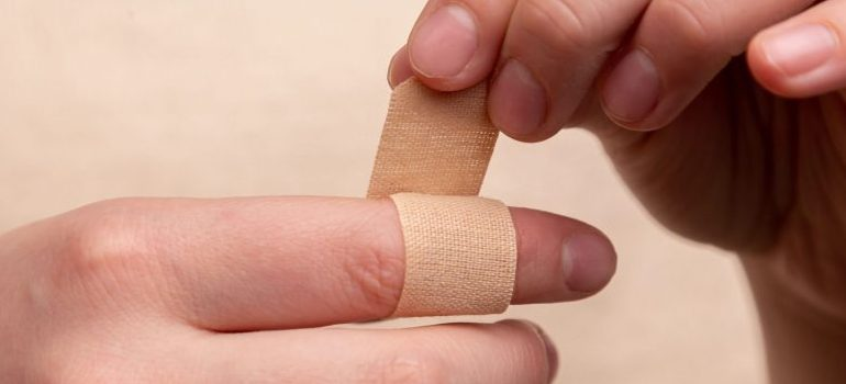 person putting a band-aid on a finger