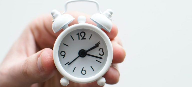 person holding a miniature clock