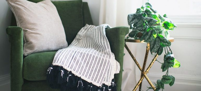 A green chair with a blanket on top.