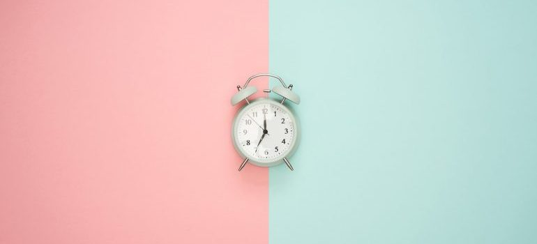 An alarm clock on a pink and blue surface.